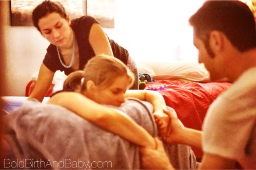 Strong mama working through labor with her husband and doula | BoldBirthAndBaby.com #boulder #doula #birth #baby